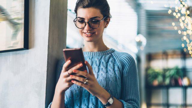 Frau nutzt Google Home auf dem Smartphone
