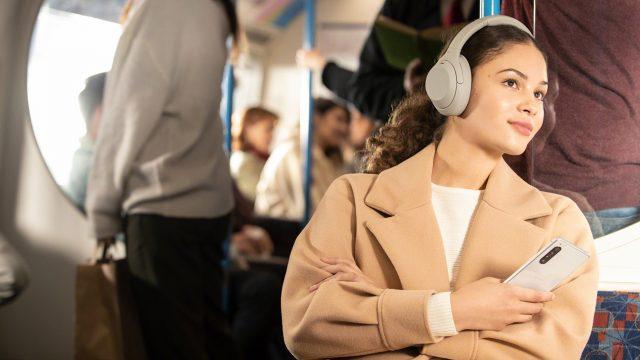 Frau nutzt Sony WH-1000XM4 in der Bahn