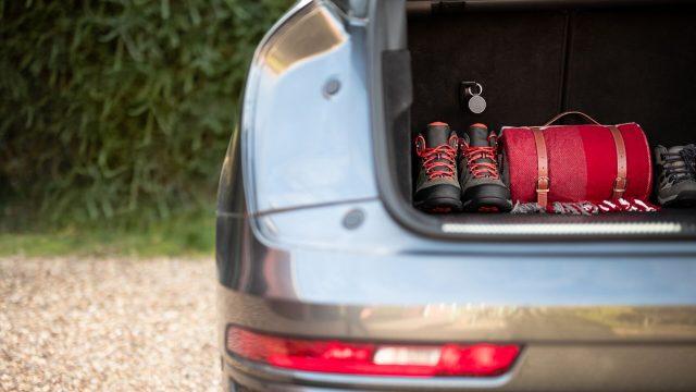Im Kofferraum eines Autos liegen Wanderschuhe und ein Rucksack, befestigt daran ist der Curve GPS-Tracker von Vodafone.