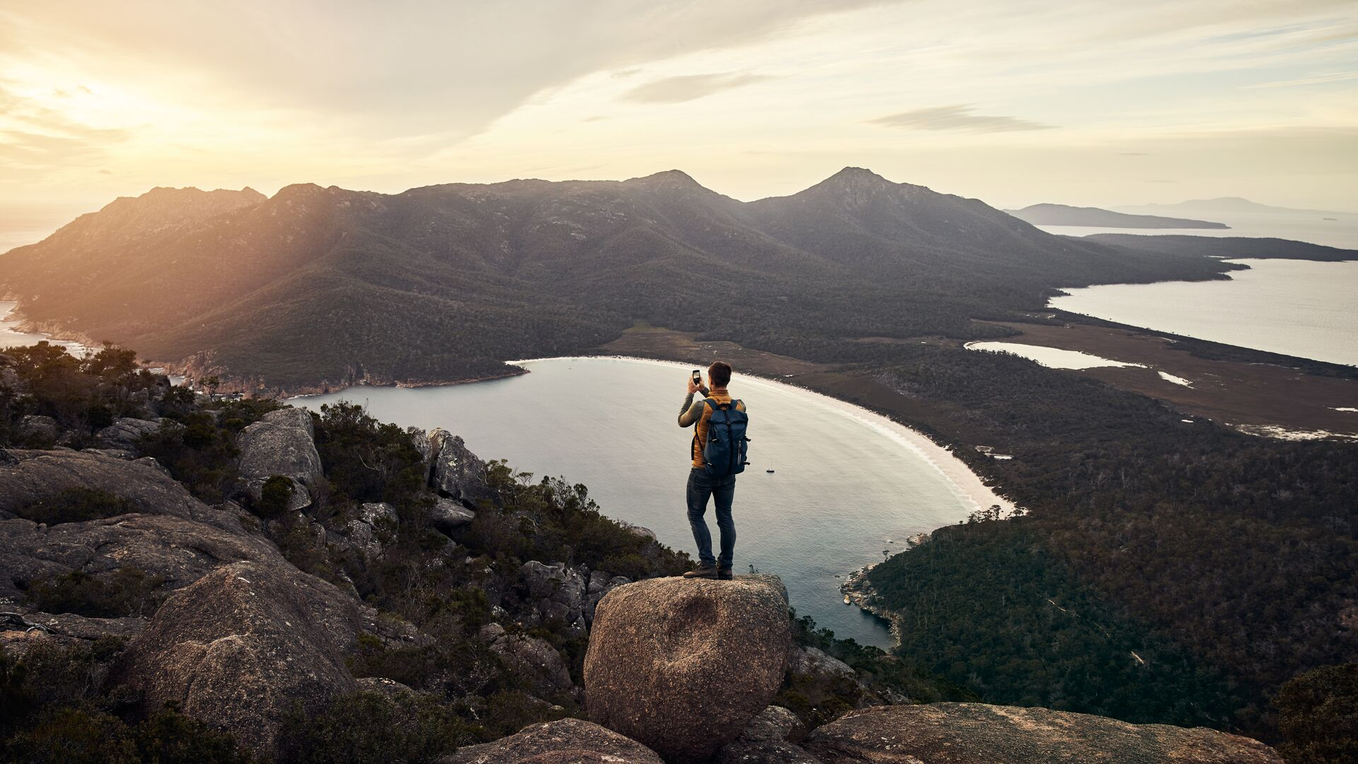 Ein Mann mit Wanderausrüstung steht auf einem Bergfels und macht ein Foto vom See, der darunter liegt.