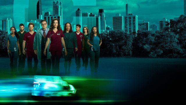 """Die Hauptdarsteller der Serie """"Chicago Med"""", zu sehen vor der Skyline Chicagos."""