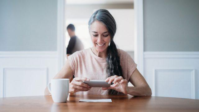 Frau scannt mit Smartphone eine Notiz ein
