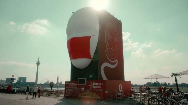 """Die Kunst-Installation """"Faces of Düsseldorf"""" von Jan Ising beim Düsseldorf Festival. Zu sehen ist ein Gesicht mit roter Corona-Maske, an der Seite LED-Animationen."""