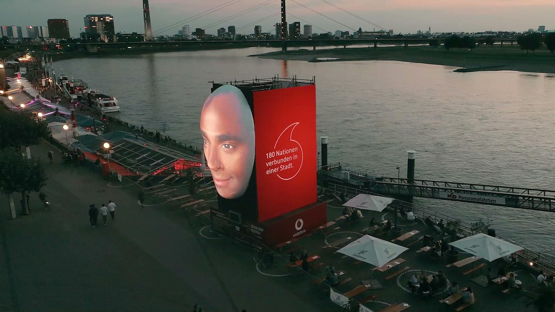"""Die Kunst-Installation """"Faces of Düsseldorf"""", zu sehen ist ein projiziertes Gesicht, daneben eine LED-Animation. Im Hintergrund ist der Rhein zu sehen."""