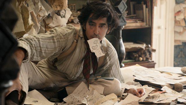 Dev Patel als David Copperfield im gleichnamigen Film inmitten von Papierstapeln, einen trägt er im Mund.