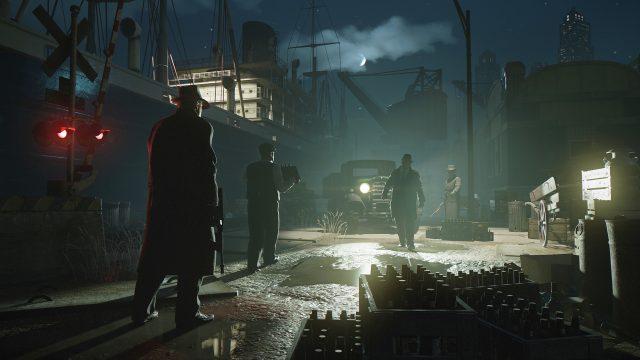"""Artwork zum Remake der """"Mafia: Definitiv Edition"""". Vier Personen stehen bei Nacht auf einem Hafengelände, eine trägt eine Waffe."""