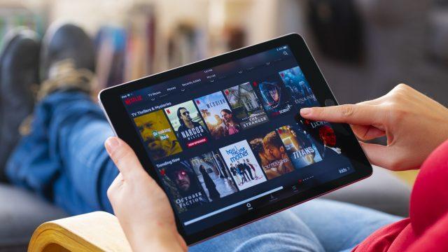 Frau nutzt Netflix auf einem Tablet