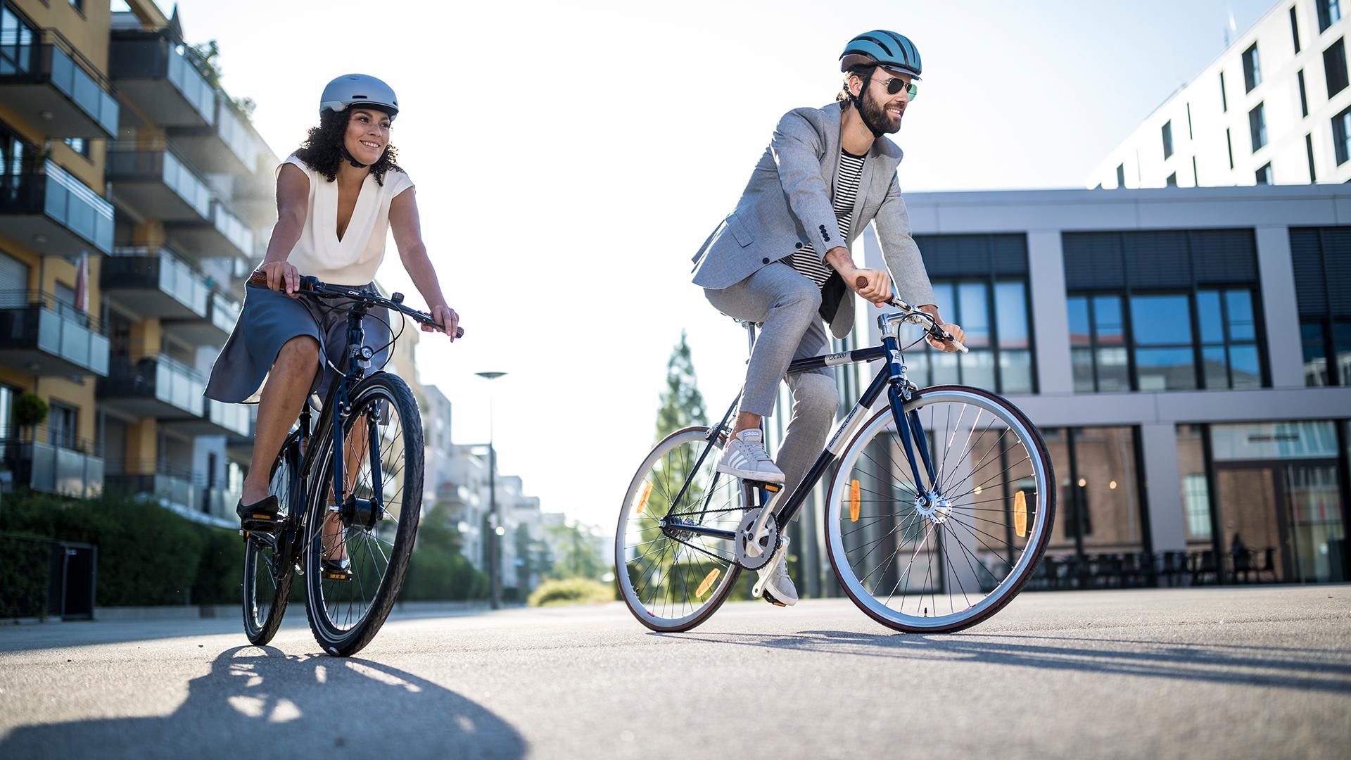 Ein Paar ist in der Stadt mit zwei Fahrrädern unterwegs.