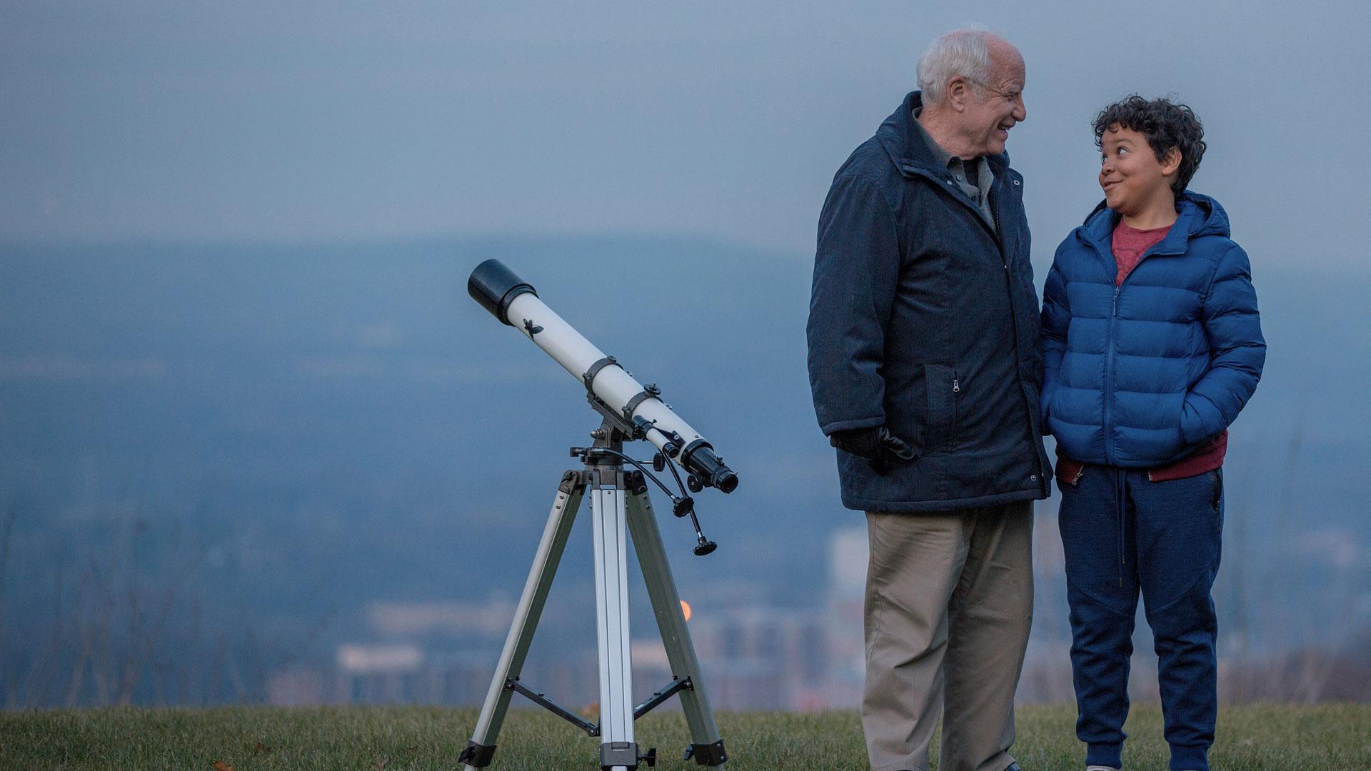Angus Stewart (Richard Dreyfuss) und sein Enkel Barney (Richie Lawrence) stehen neben einem Teleskop