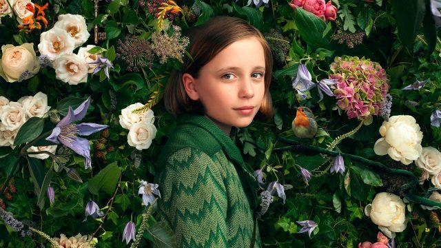 """Das Mädchen Mary (Dixie Egerickx) vor einer Blumenhecke im Film """"Der geheime Garten""""."""