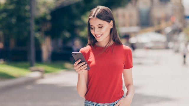 Junge Frau schaut auf ihr Android-Smartphone