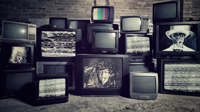 Mehrere Röhrenfernseher stehen gestapelt aufeinander, auf einigen sieht man schreiende Gesichter und eine Bildstörung.