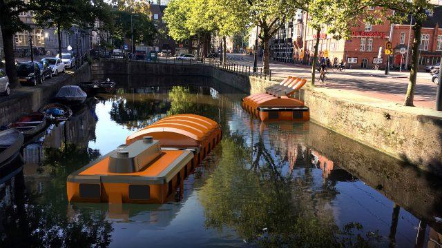"""Eine 3D-Simulation des autonom fahrenden Roboter-Boots """"Roboat"""" schwimmt in einer Gracht in Amsterdam."""