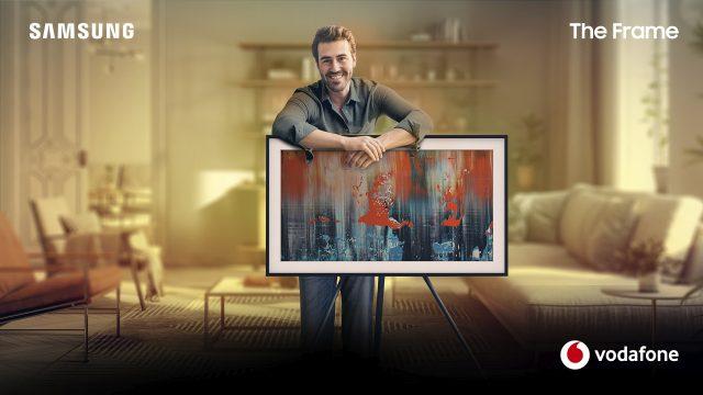 """Ein Mann lehnt über seinem Fernseher, den Samsung """"The Frame"""", der ein Kunstwerk zeigt."""