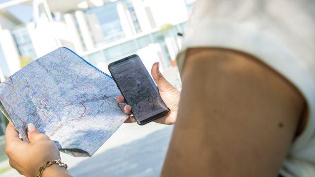 Frau hält Smartphone und Karte