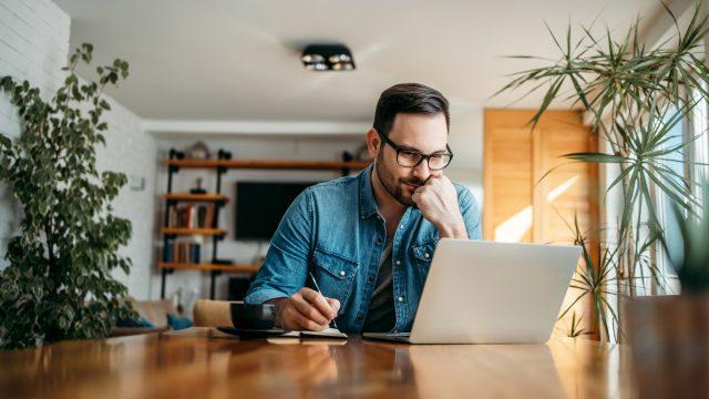 Mann sitzt im Wohnzimmer al Laptop