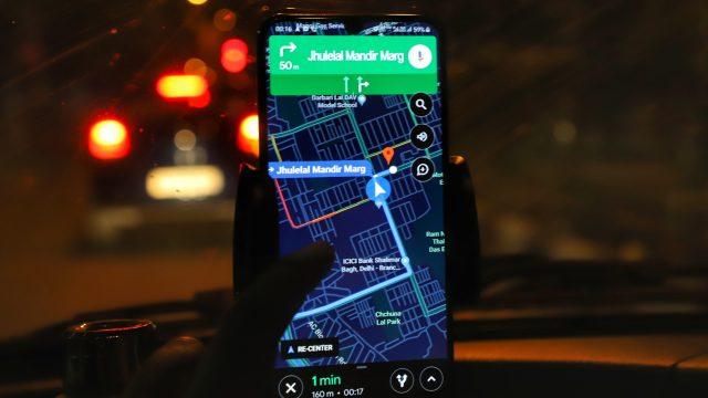 Smartphone mit Google Maps im Auto bei Nacht