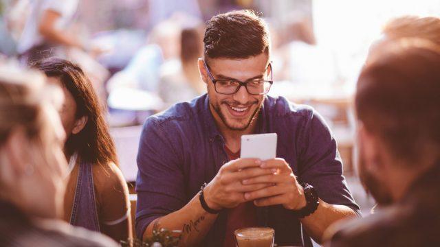 Mann sendet Geld per PayPal mit dem Smartphone