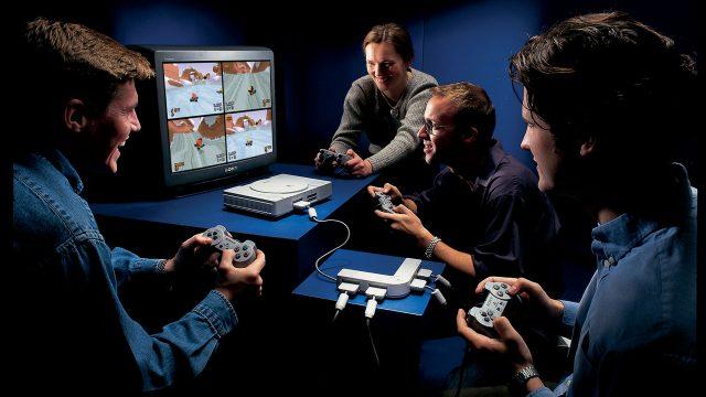 Vier Leute spielen gemeinsam an der ersten Sony PlayStation ein Spiel.