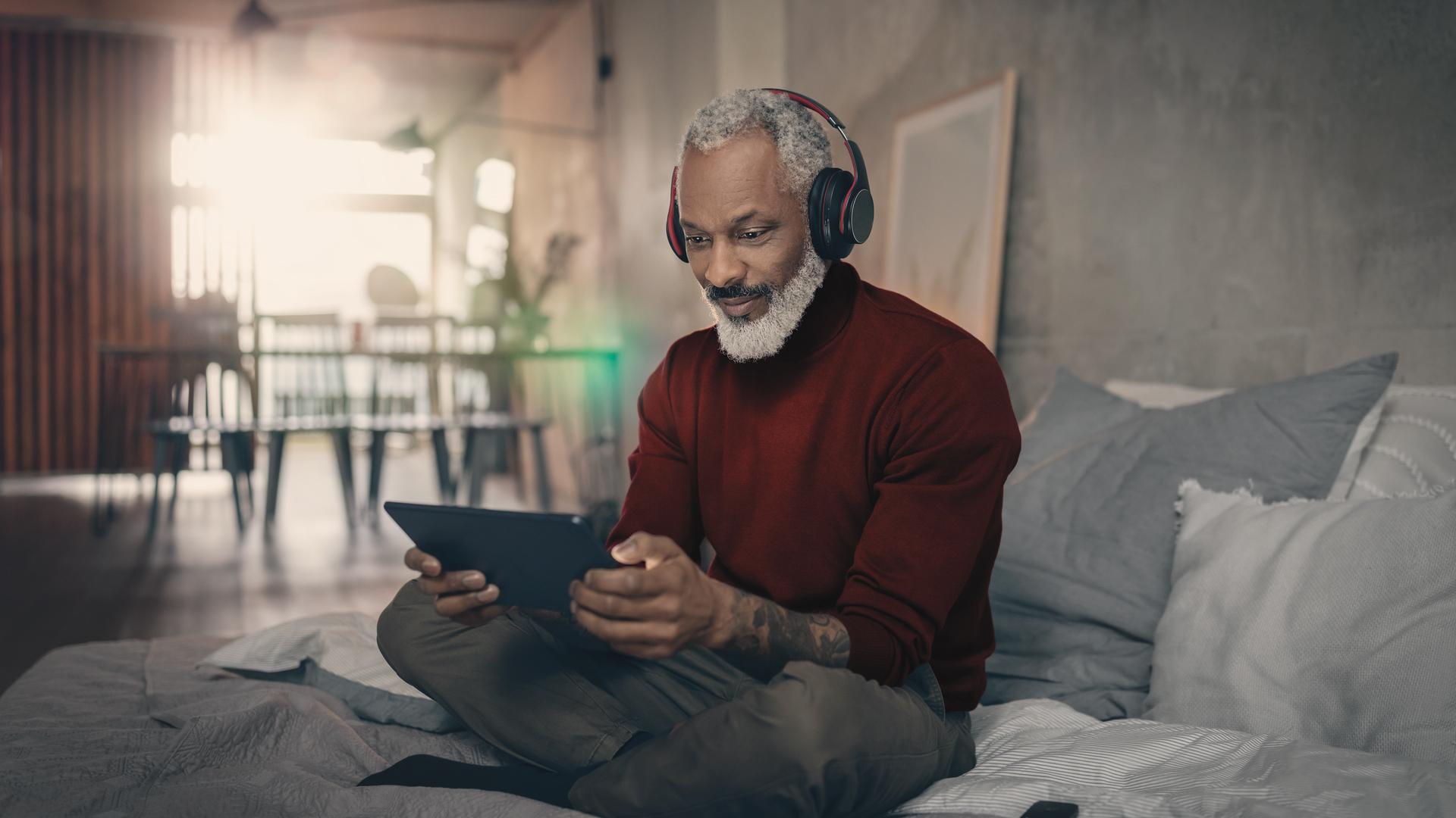 Ein Mann sitzt mit Kopfhörern und seinem Tablet auf dem Bett.
