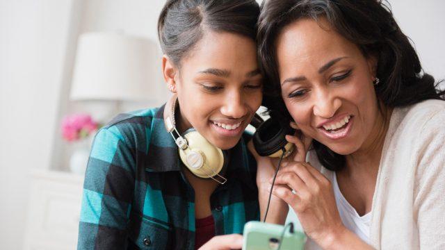 Mutter und Tochter hören Musik über Smartphone