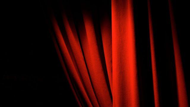 Ein roter Vorhang lüftet sich.