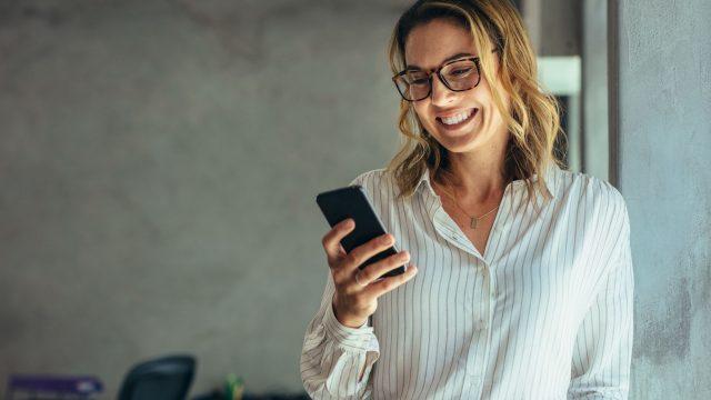 Frau macht Screenshot mit Handy.