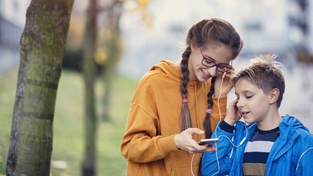 Bruder und Schwester hören Spotify Family auf dem Smartphone