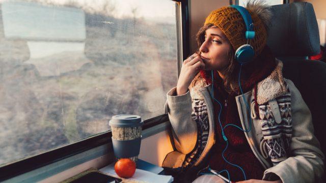 Frau hört im Zug Musik mit Spotify