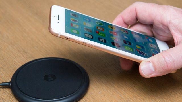 Hand legt iPhone 8 Plus auf Ladestation