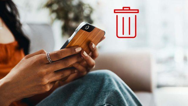Frau bedient Smartphone, Symbolbild mit Papierkorb-Emoji