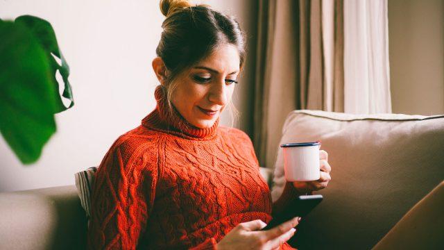 Eine Frau liegt mit einem Heißgetränk auf der Couch und surft auf ihrem Smartphone.