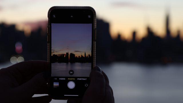 Smartphone fotografiert Skyline von New York im Sonnenuntergang