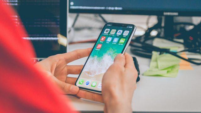 Mann am Schreibtisch, hält iPhone in der Hand