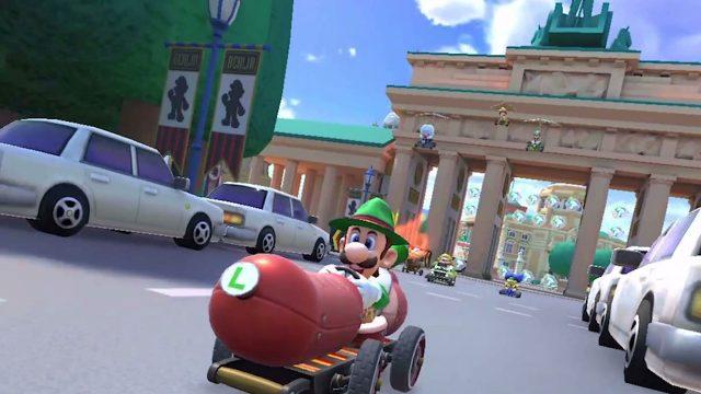 """Game-Screenshot aus """"Mario Kart Tour"""": Luigi fährt mit seinem Wagen vor dem Brandenburger Tor in Berlin."""