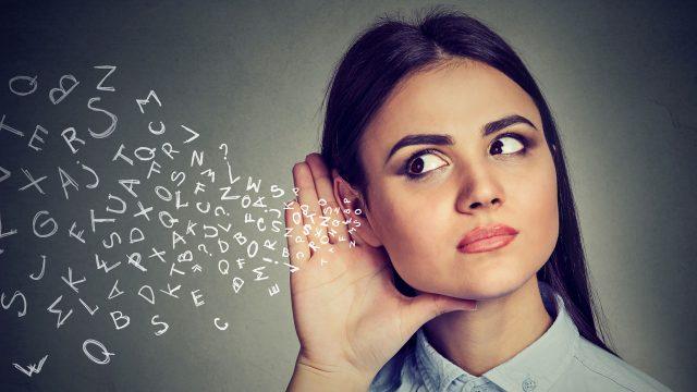 Eine Frau hält ihre Hand ans Ohr und lauscht. In ihr Ohr fließen Buchstaben.