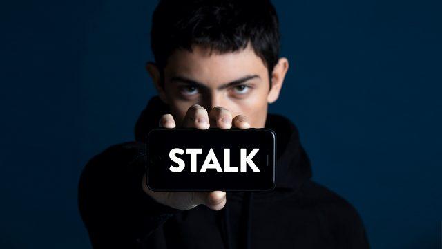 """Théo Fernandez als Lucas in der drama-Serie Stalk. Er hält ein Smartphone, auf dem """"STALK"""" zu lesen ist, in die Kamera."""