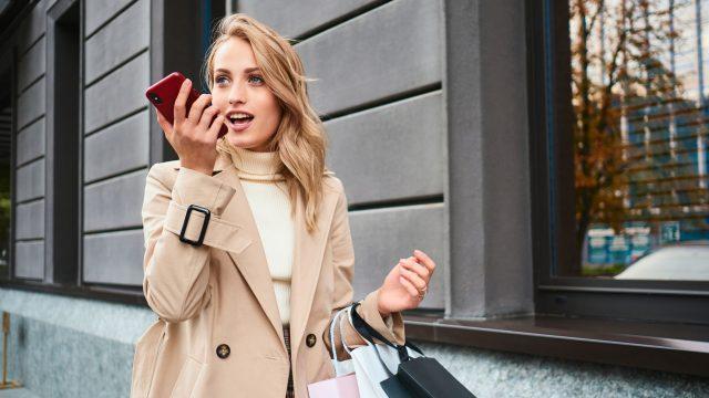 Frau mit Einkaufstüten spricht einen Kurzbefehl für Siri ins iPhone