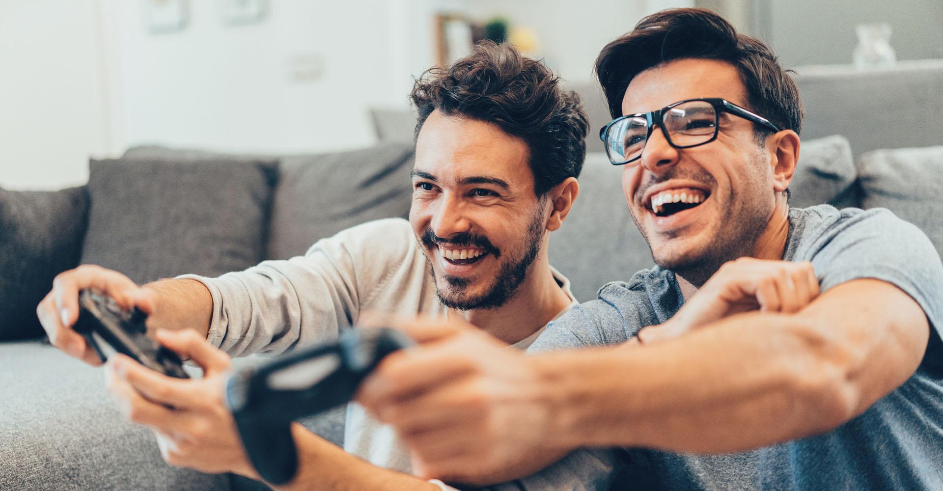 Zwei junge Männer spielen ein Game auf der PlayStation