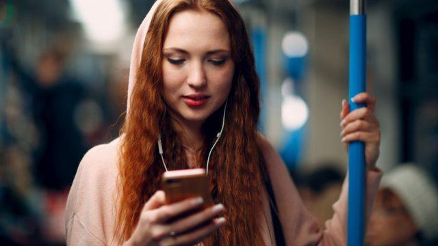 Frau hört Musik am Handy via Spotify.
