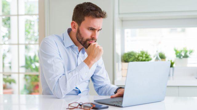 Mann sitzt konzentriert an seinem Laptop