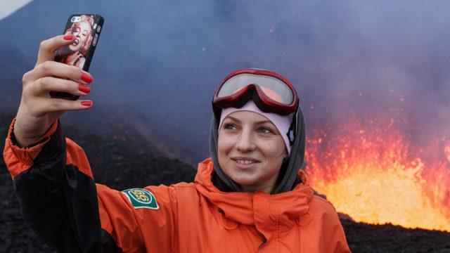 Frau macht Selfie vor ausbrechendem Vulkan