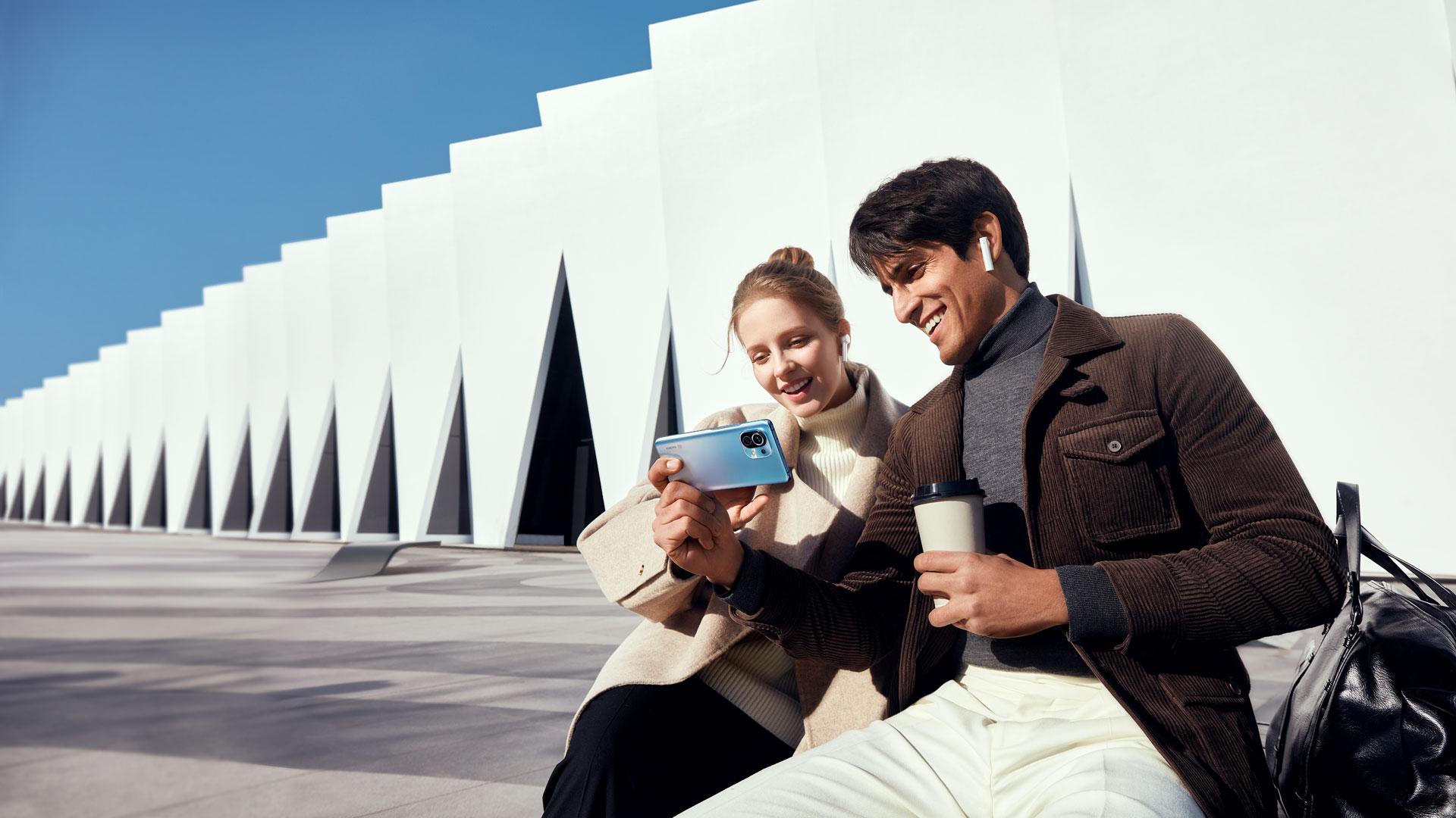 Ein Mann zeigt einer Frau eine Inhalt auf seinem Xiaomi Mi 11 | 5G, er trägt Kopfhörer und hält einen Kaffeebecher.