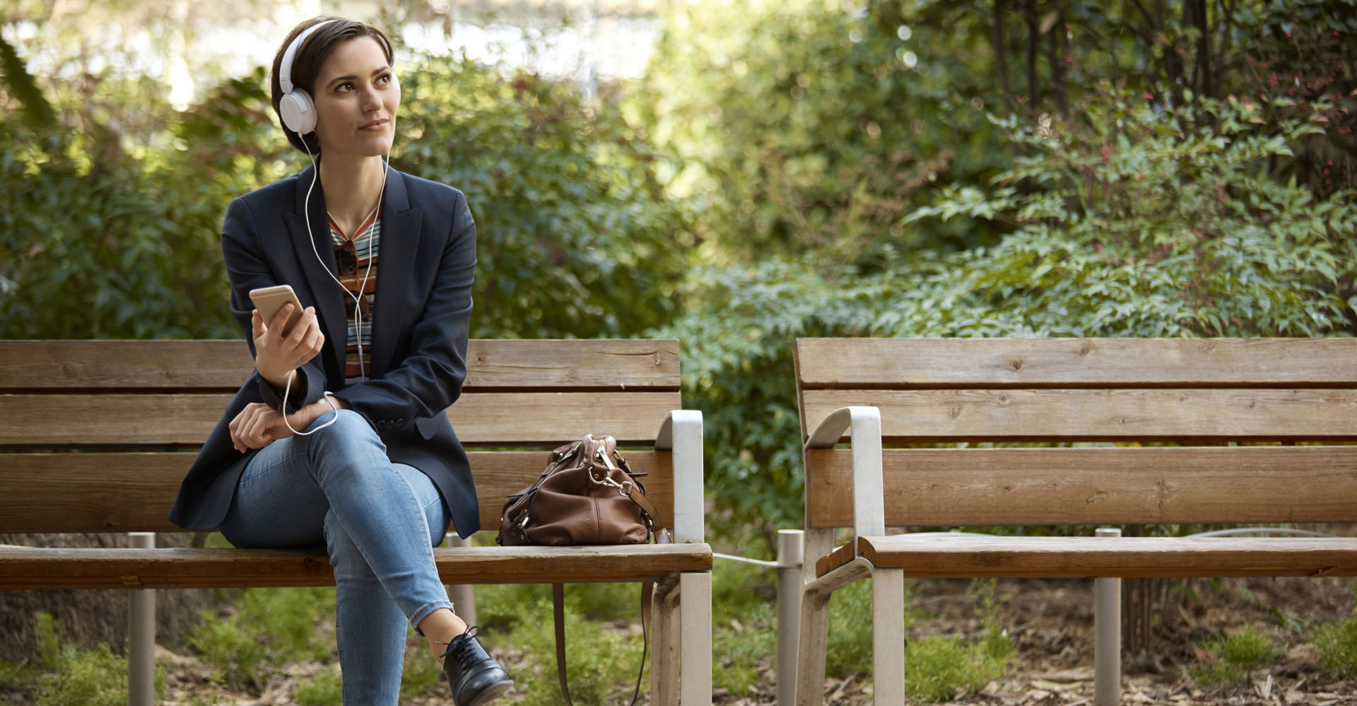 Frau sitzt auf einer Parkbank und hört Musik