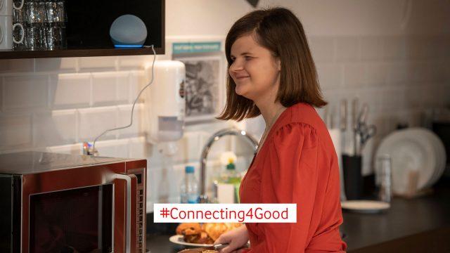 Eine Frau bereitet etwas in der Küche zu und hört einer Audiodeskription über ihr Alexa-Gerät zu.