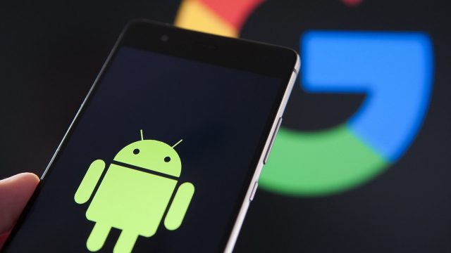 Android-Männchen auf einem Smartphone, Google-Symbol im Hintergrund