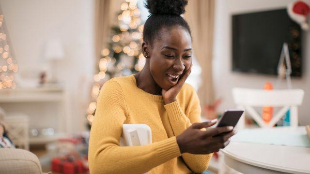Frau führt Videoanruf mit dem Smartphone und ist ganz entzückt