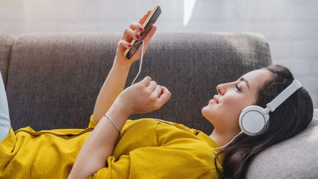 Frau liegt auf dem Sofa und hört mit dem Smartphone Musik