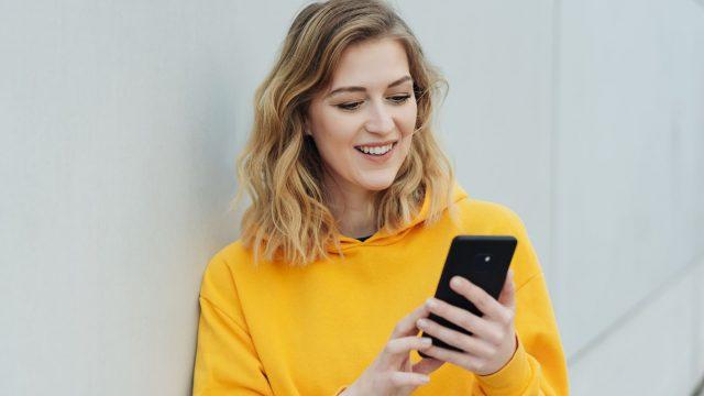 Junge Frau schaut auf ihr Android-Handy.