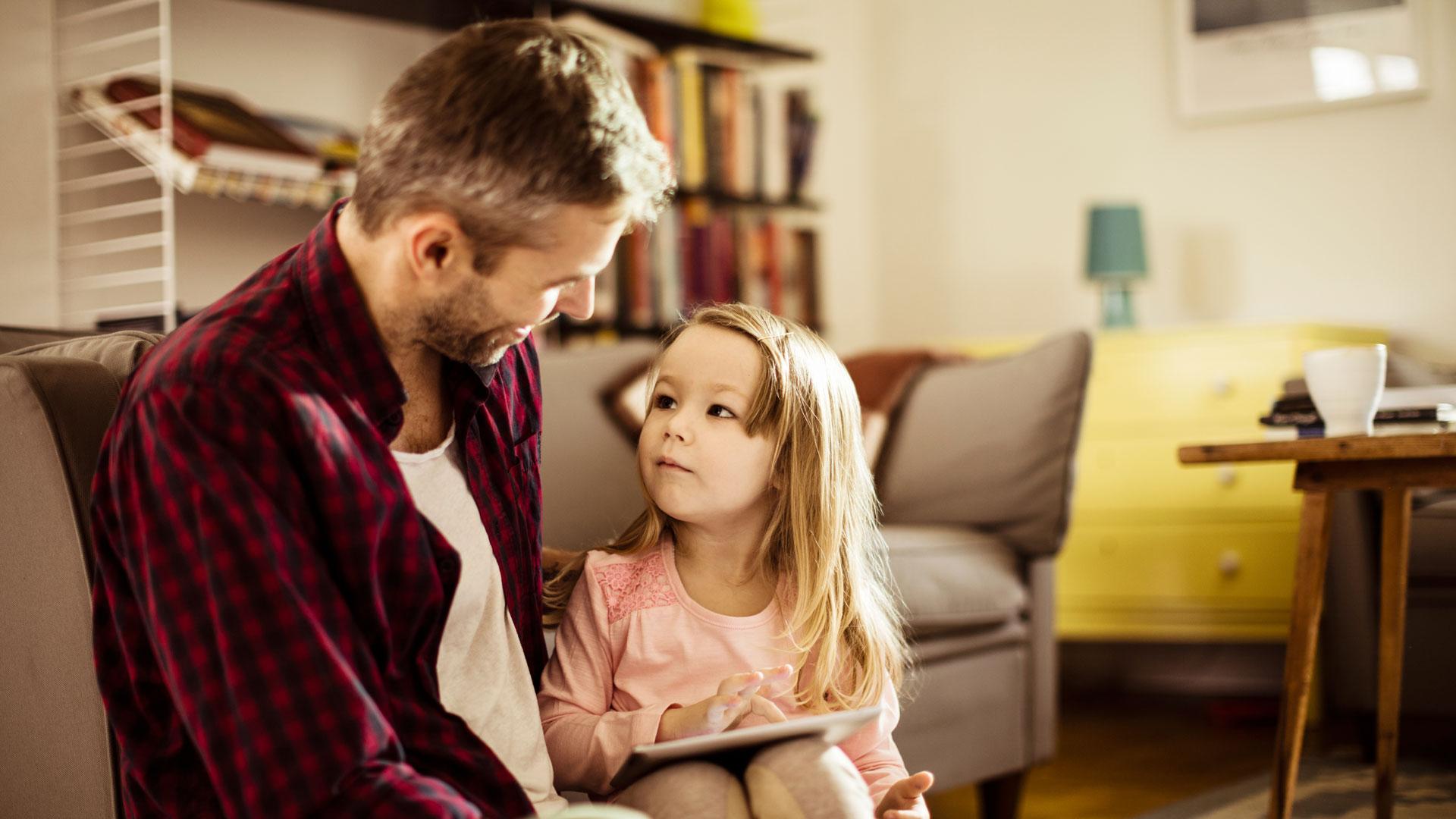 Vater schaut mit seinem Kind auf ein Tablet.